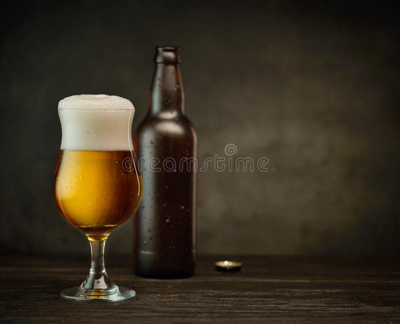 Beer glass and bottle. On dark pub table royalty free stock images