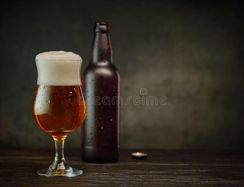 Beer glass and bottle. On dark table and wall background stock photos