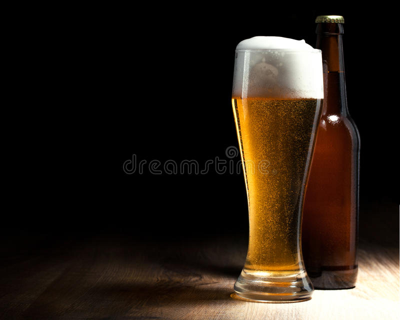 Beer glass and bottle on a wooden table. And black royalty free stock image
