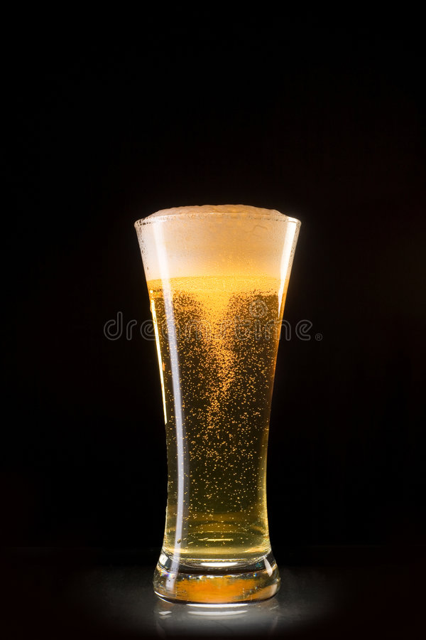 Beer glass with bubbles whirl. Isolated on black background stock photo