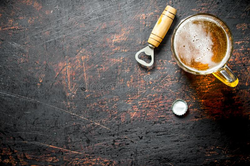 Beer in a glass cup and opener. On dark rustic background royalty free stock images