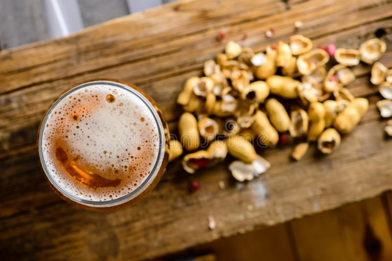 Beer glass with dark cold beer with bubble froth and peanuts on. The table. Top view, flat lay royalty free stock images