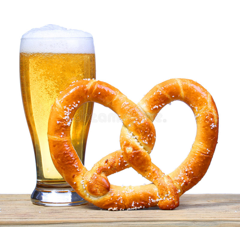 Beer Glass with German Pretzel on wooden table. isolated. On white royalty free stock photo