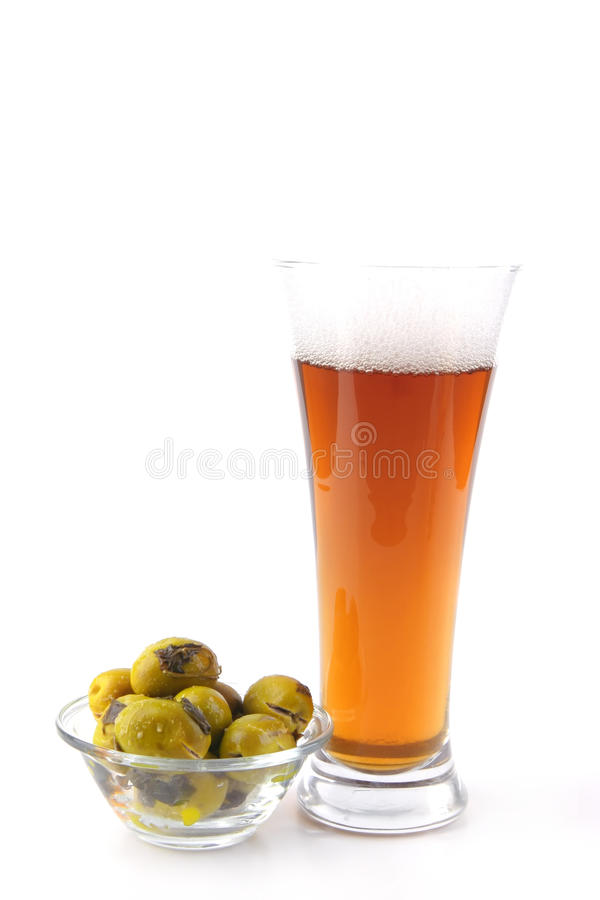 Beer glass with gold olives stock images