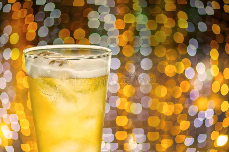 Beer on a glass with golden bokeh on background. time to celebrate festival for hang out. time to chill out with friend concept. Image for background royalty free stock photography