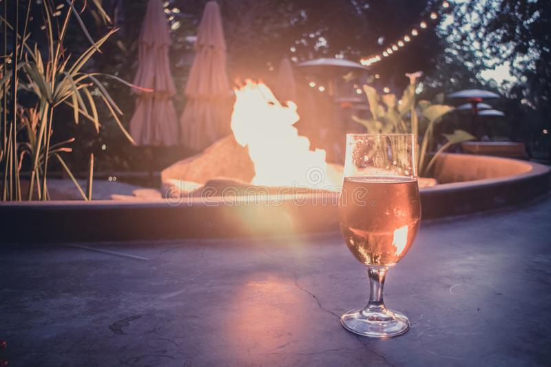 Beer glass illuminated by fire pit in background stock photography