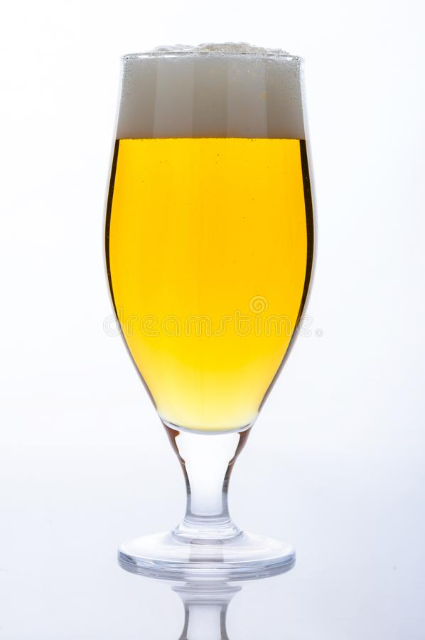 Beer glass with light cold beer with bubble froth on light backg royalty free stock photo