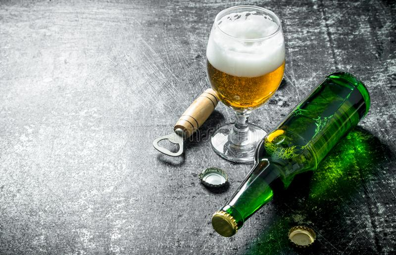 Beer in a glass with opener. On black rustic background royalty free stock photos
