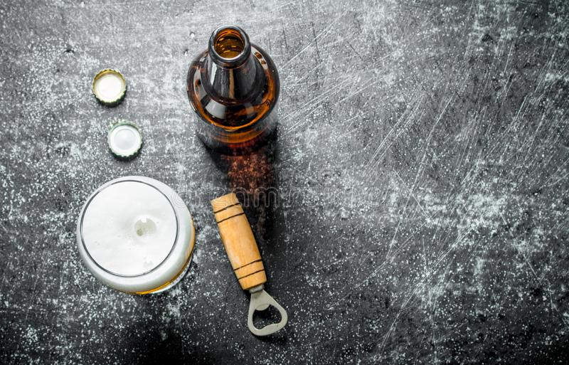 Beer in a glass with opener. On black rustic background royalty free stock images