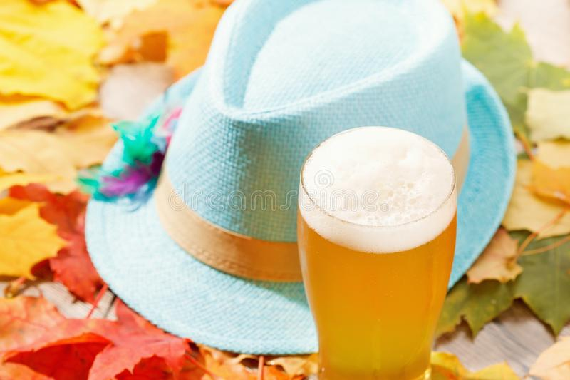Beer glass pint octoberfest picnic on background with hat and autumn leaves. Beer glass pint octoberfest picnic on background with hat and autumn yellow leaves royalty free stock photos