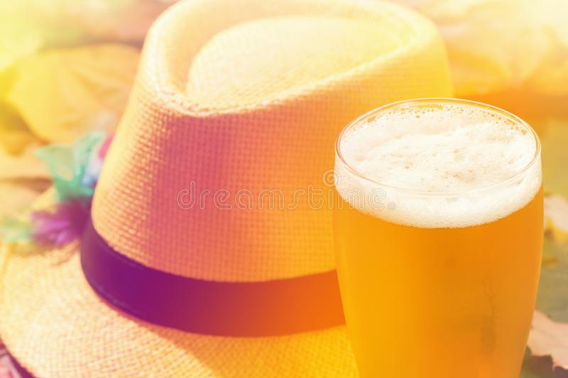 Beer glass pint octoberfest picnic on background with hat and autumn leaves. Beer glass pint octoberfest picnic on background with hat and autumn yellow leaves royalty free stock image