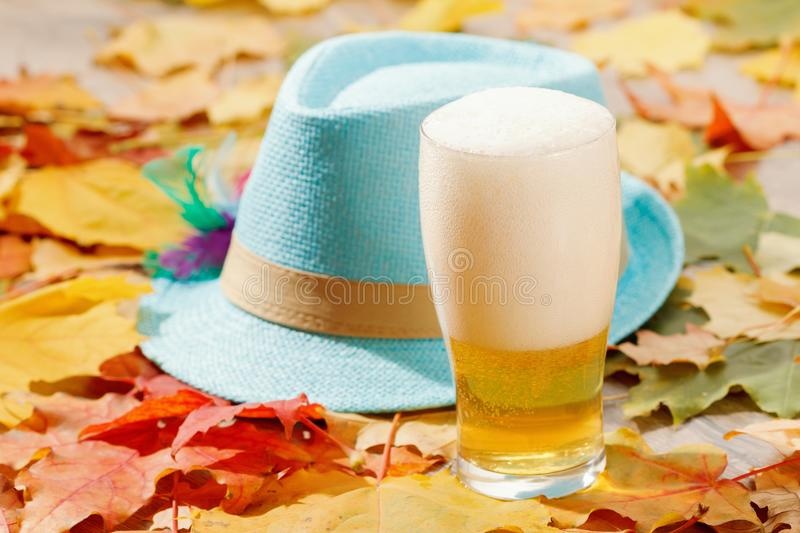 Beer glass pint octoberfest picnic on natural background with hat and autumn leaves. Beer glass pint octoberfest picnic on natural background with hat and autumn royalty free stock photo