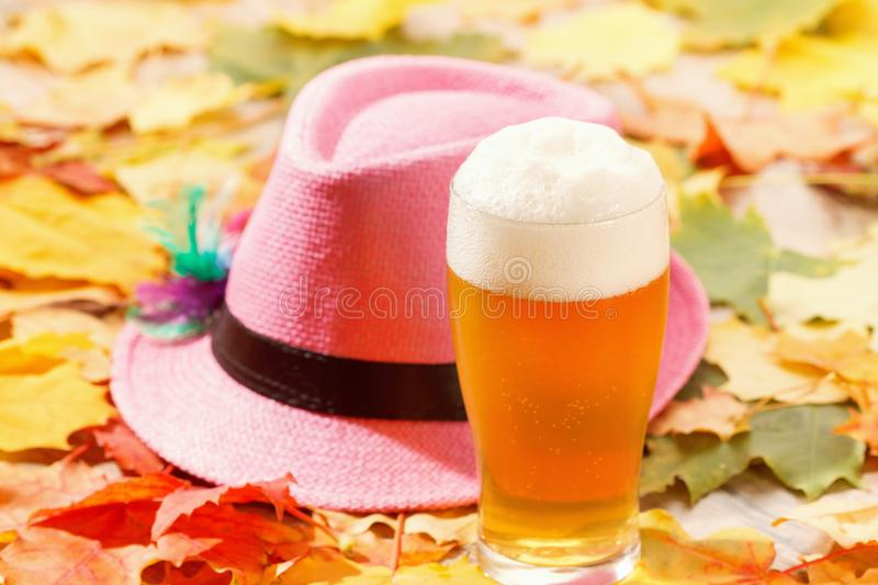 Beer glass pint octoberfest picnic on natural background with hat and autumn leaves. Beer glass pint octoberfest picnic on natural background with hat and autumn royalty free stock photography