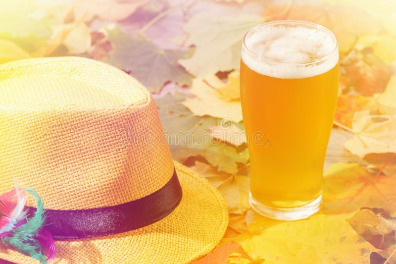 Beer glass pint octoberfest picnic on natural background with hat and autumn leaves. Beer glass pint octoberfest picnic on natural background with hat and autumn royalty free stock photos
