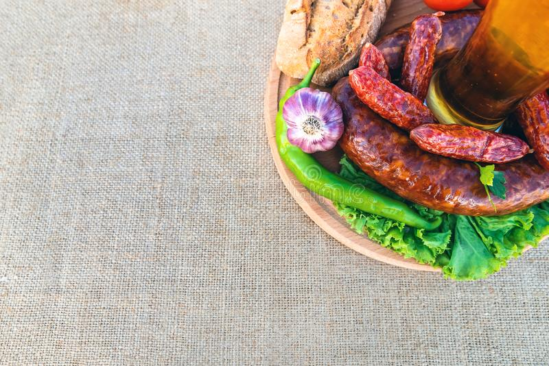Beer in a glass, sausage, vegetables on a table stock image