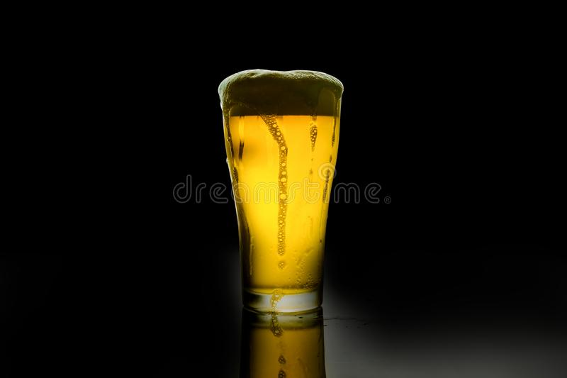 Beer glass with white foam. On dark background stock photography