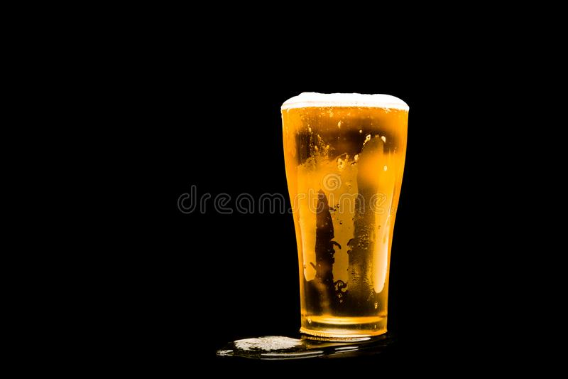 Beer glass with white foam. On dark background stock photo