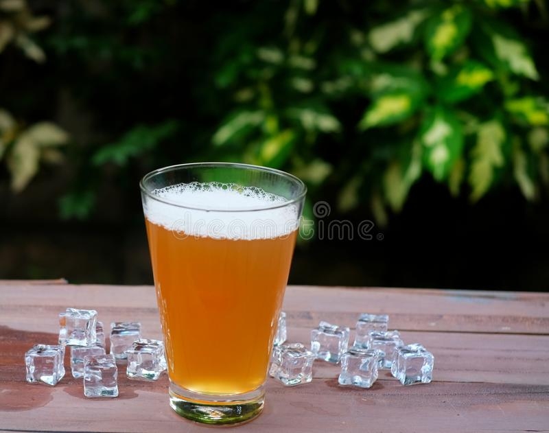 Beer in glass on wood table with ice, car background. royalty free stock image