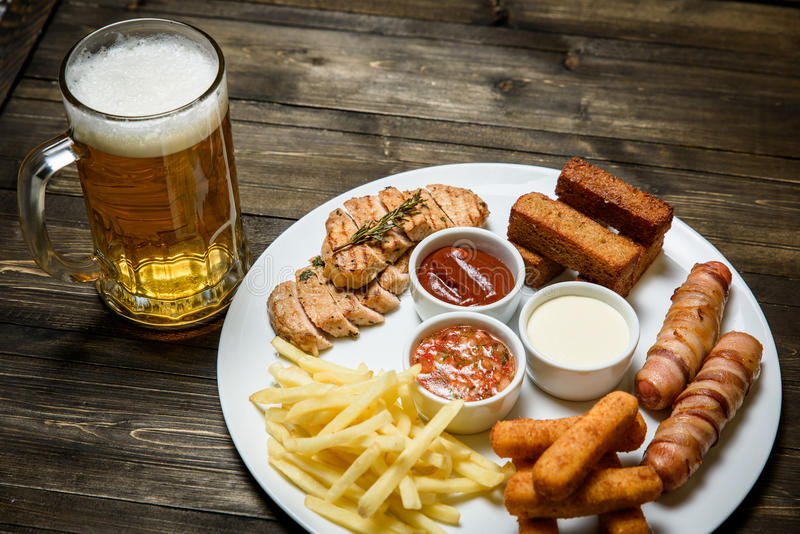 Beer in a glass on wooden background. and snack. stock photography