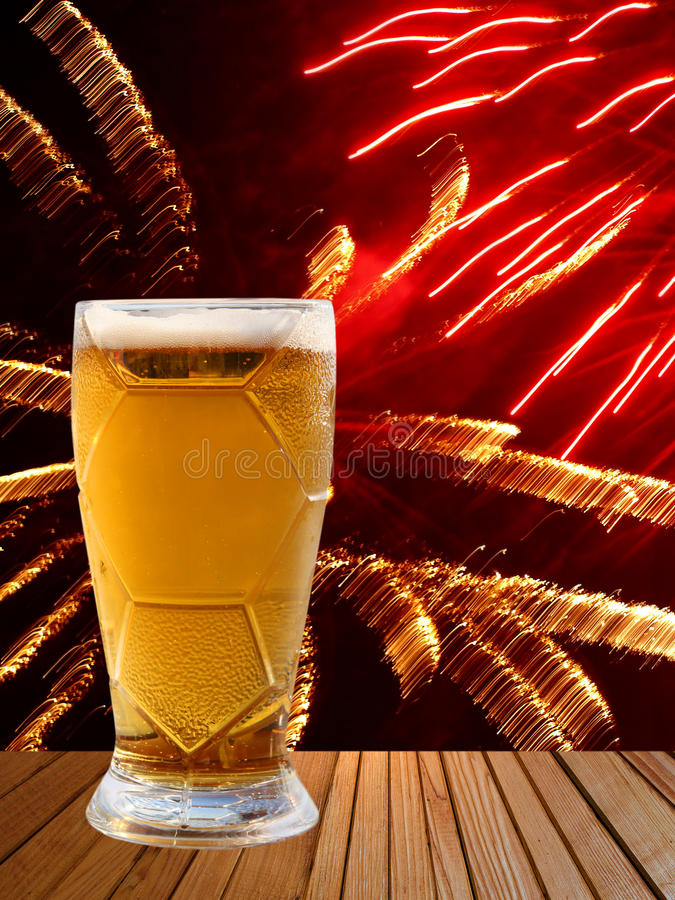 Beer glass on wooden table against of multicolored fireworks. royalty free stock images