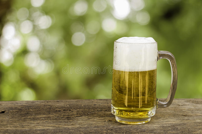 Beer in glass on wooden table with blurred green summer leaves o. royalty free stock photo