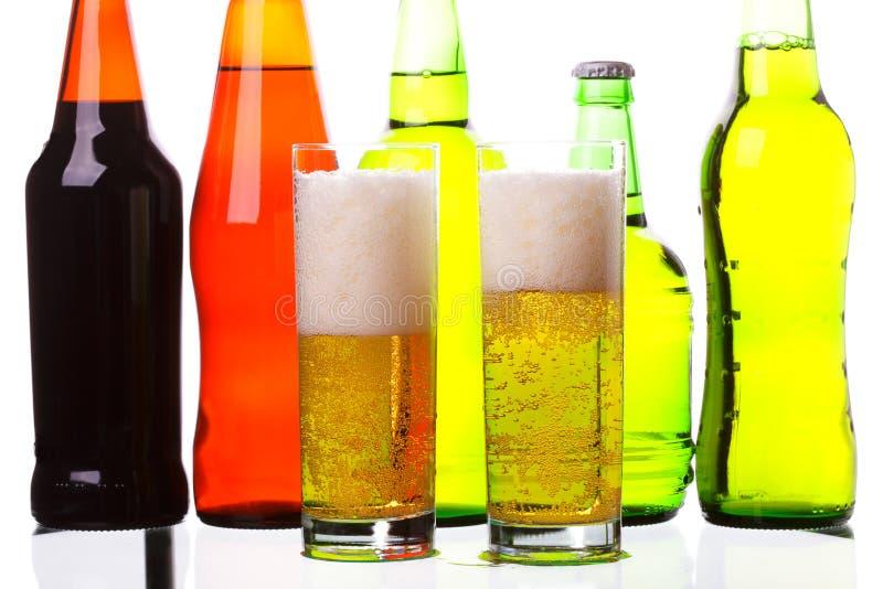 Beer glasses against bottles royalty free stock photo