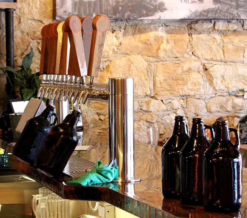 Beer growlers being filled up on a bar at a micro brew house tap room. stock images