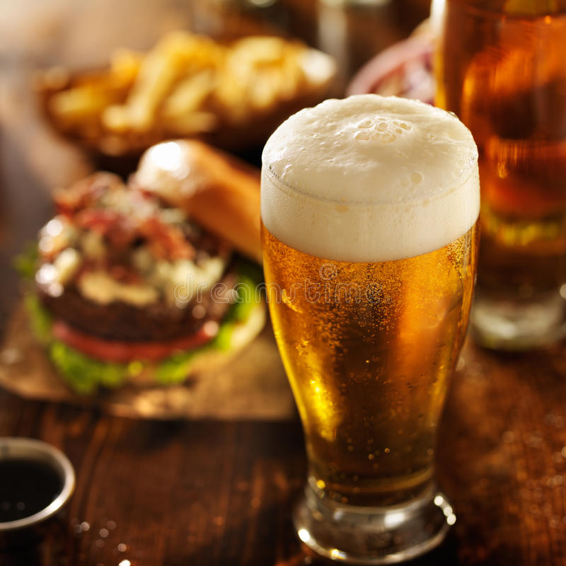 Beer with hamburgers on restaurant table. Shot in warm light with selective focus stock image