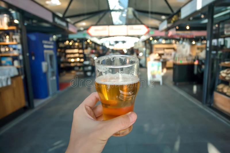 Beer in hand of visitor inside central food market of Copenhagen, Denmark. Many stores with drinks and delicacy food.  stock images
