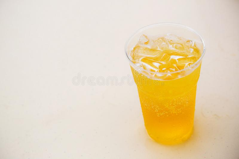 Beer with ices in glass on the white table.Glass of beer on white table in Golden Light. stock image