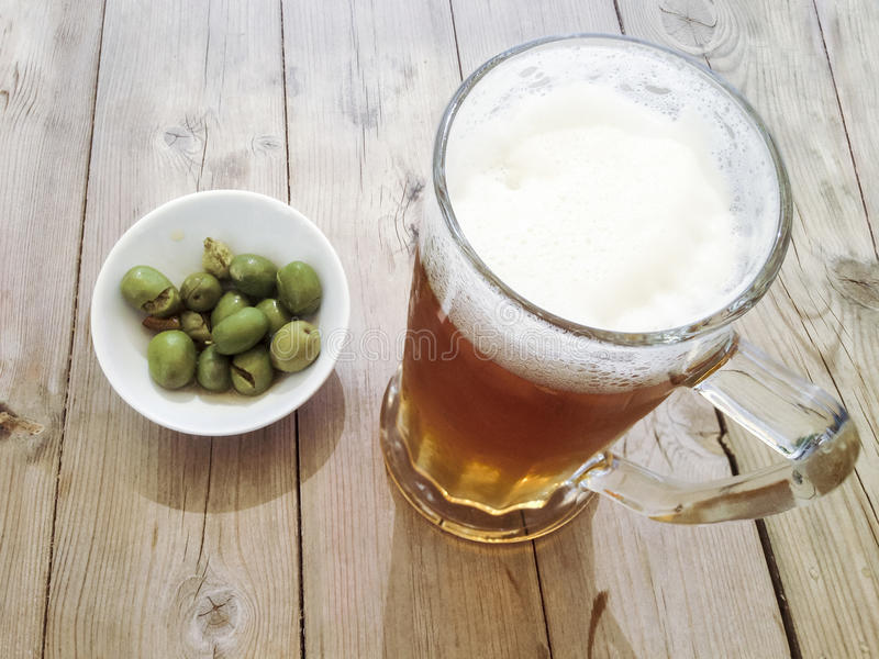 Beer jar with little plate of green olives. Typical snack for sp stock image
