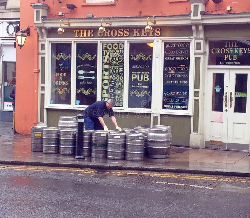 Beer kegs being delivered at a Public house. A man sorting beer kegs that have been delivered to a public house. The barrels are outside. This is a public house royalty free stock photography
