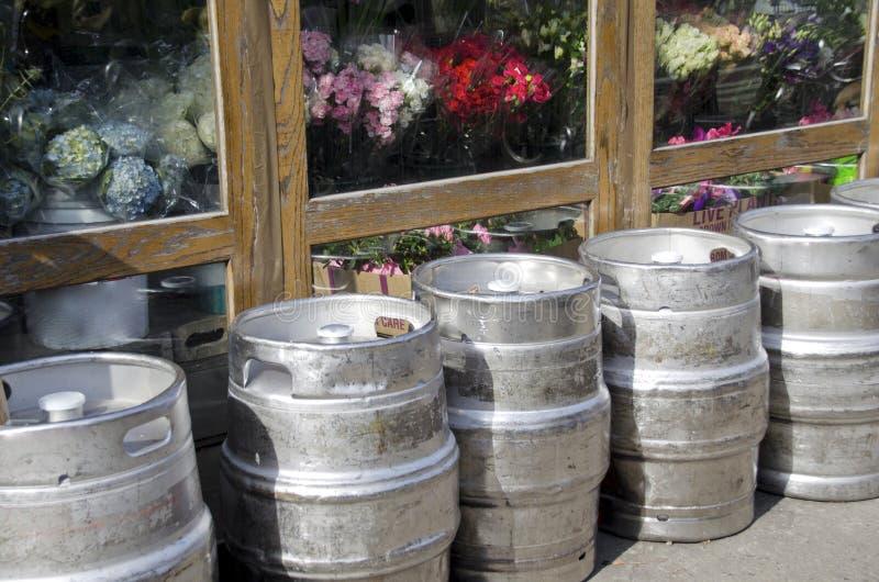 Beer Kegs. Empty beer kegs lined up outside a flower store stock image