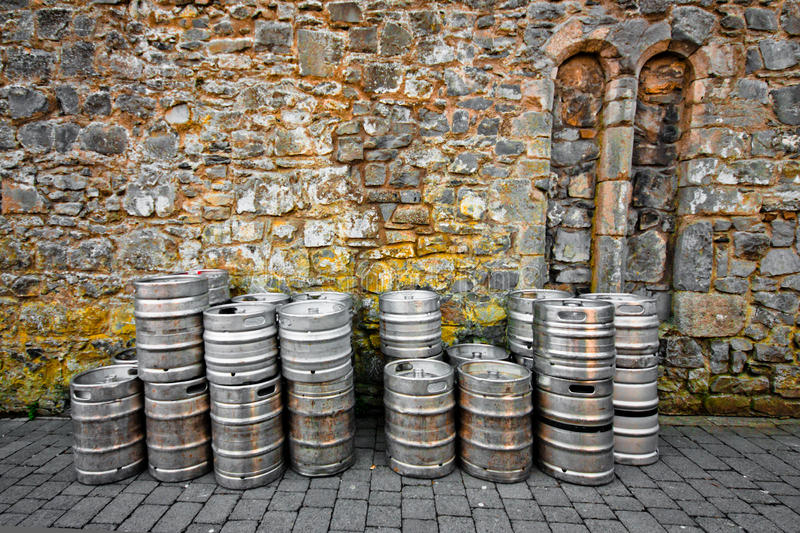 Beer Kegs. Stack of beer kegs against a rustic stone wall royalty free stock images