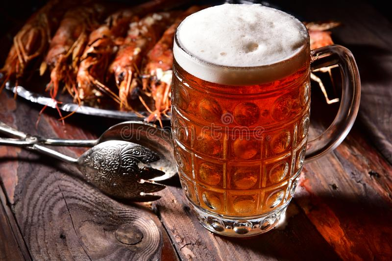 Beer and langoustines on a dark background. stock photography