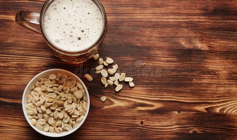 Beer in a mug and snack. Beer light in a mug and a different dry salty snack stock photos