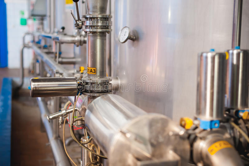 Beer manufacture line. Equipment for staged production bottling of Finished food products. Metal structures, pipes and tanks at en stock photo