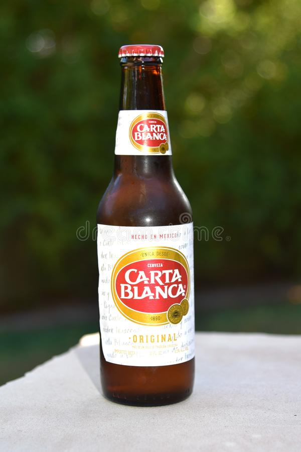 Bottle of Carta Blanca beer imported from Mexico. Beer manufactured in Mexico exported to the United States. Free trade agreement keeps from tariffs royalty free stock images