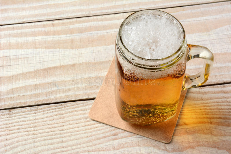 Beer in a Mason Jar. High angle closeup of a mason jar full of beer on a rustic wood table stock photos
