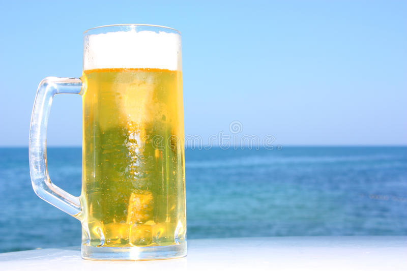 A beer mug. A beer in mug isolated on a blue sea and sky background royalty free stock images