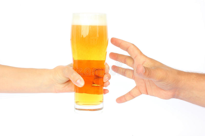 A beer mug. A woman`s hand give a beer mug to a male hand isolated on a white background royalty free stock photography