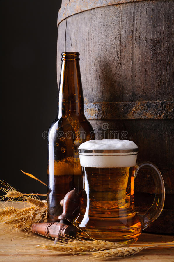 Beer mug and bottle. Still life with beer mug, bottle, grain and wooden barrel royalty free stock photos