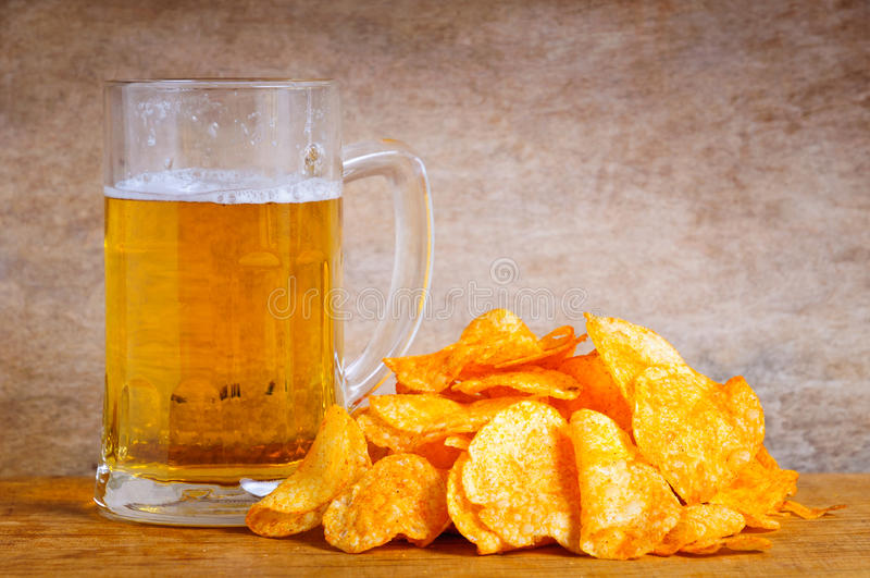 Beer mug and chips. Beer mug and potato chips on a wooden background royalty free stock image