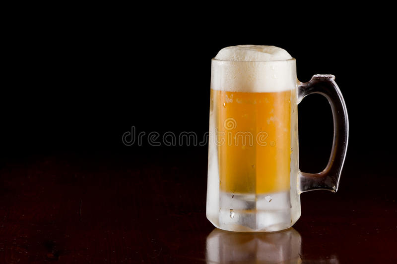 Beer mug. Cold beer served in a frozen mug on a bar top isolated on a black background stock photo