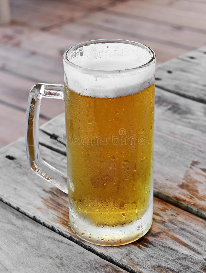 Beer mug. Cold beer in a mug on a wooden table royalty free stock images
