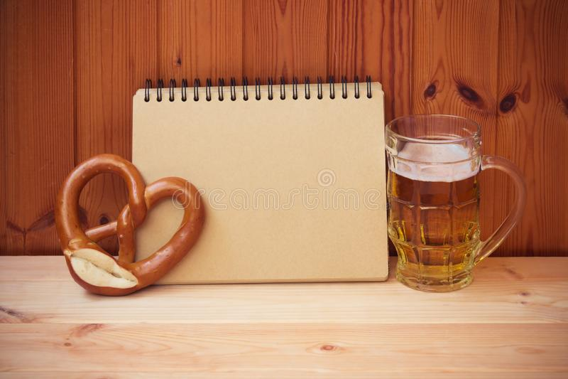 Beer mug, empty notebook and pretzel on wooden table. royalty free stock photography