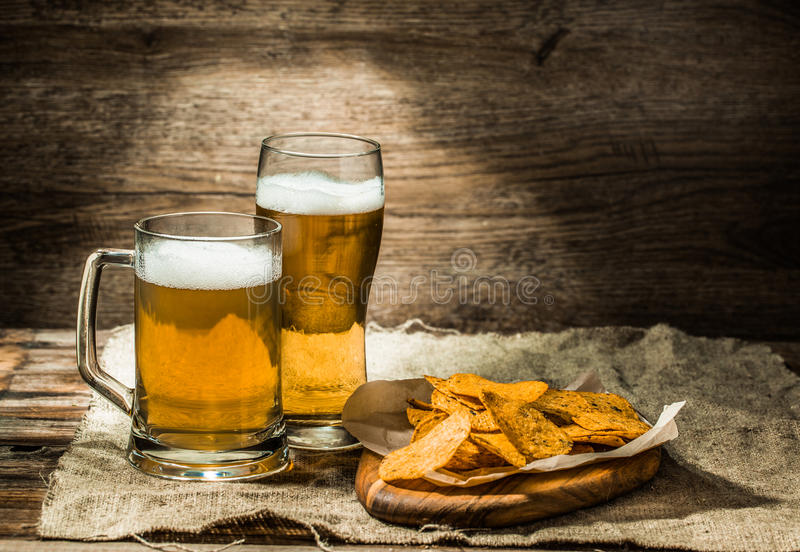 Beer in a mug, glass , chips on board. Beer in a mug, glass , potato chips on board royalty free stock images