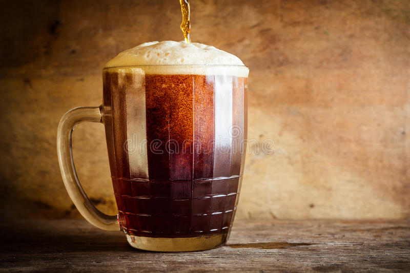 Beer in mug on rustic wooden background. Side view and copy space stock images
