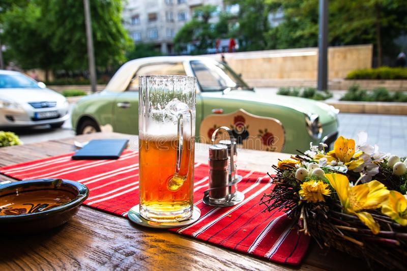 Beer mug on table in cafe garden stock image