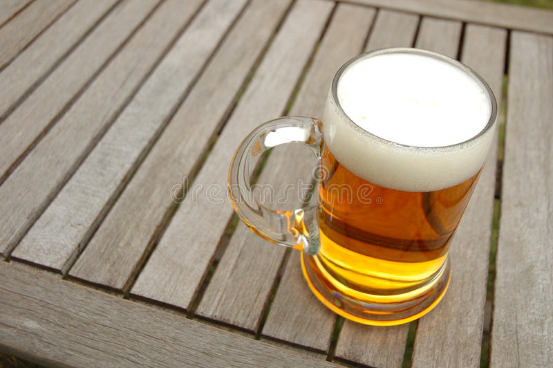 Beer mug on table. Beer mug on wooden table outdoors royalty free stock photography